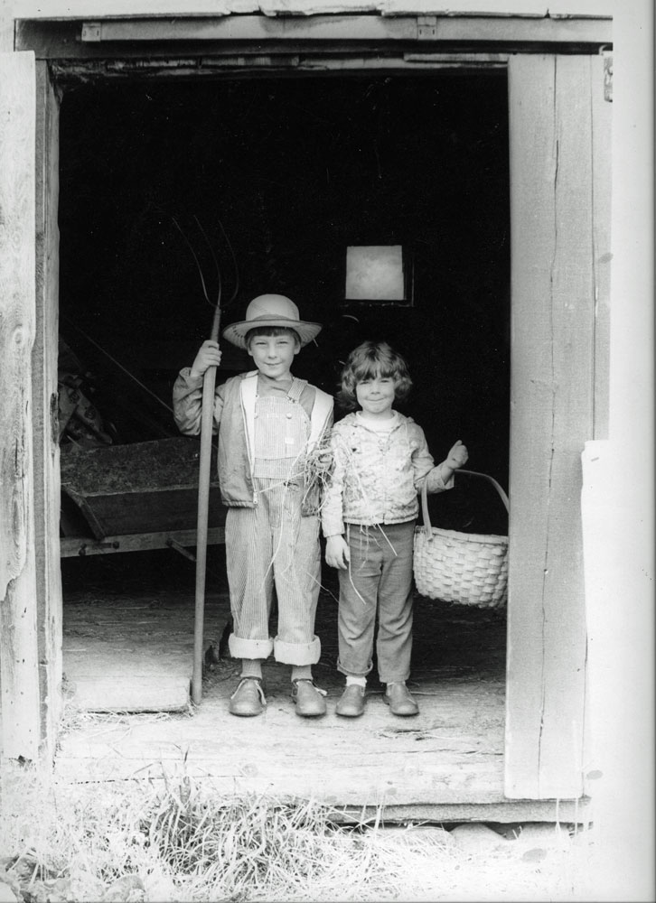 Photo of boy and girl standing in the doorway of a barn