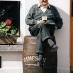 Photo of older man sitting on top of whiskey barrel drinking stout