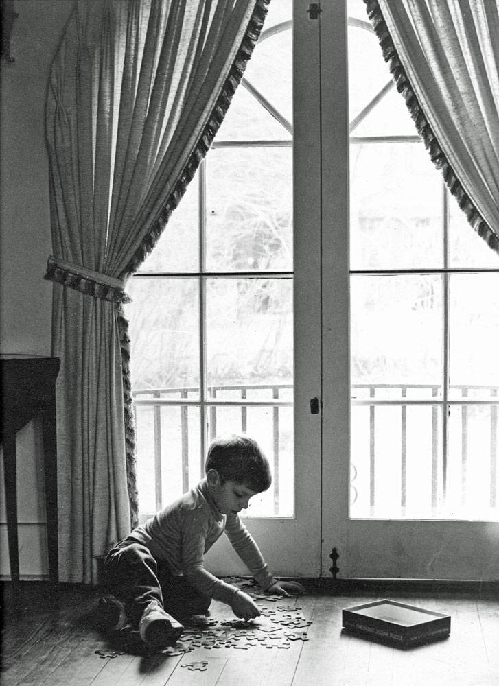 Photo of boy doing a jigsaw puzzle in front of windows