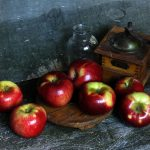 Photo of apples, glass bottle, antique coffee grinder