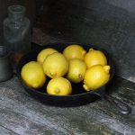 Photo of lemons, cast iron pan, tin cup, glass bottle