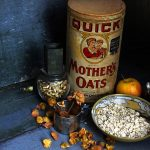 Photo of dry oats in ceramic bowl, antique nut grinder, dried roses, antique oats container, apple