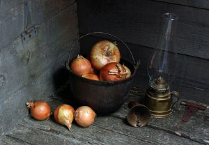 Photo of onions, cast iron pot, antique handbell, and hurricane lamp