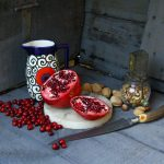 Photo of pomegranate, antique nut grinder, ceramic pitcher, cranberries, walnuts