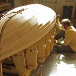 Photo of boat builder working on small wooden boat